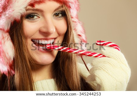 Young woman holding sweet candy cane in mouth. Girls hands wear woolen white gloves. Christmas time concept. - stock photo