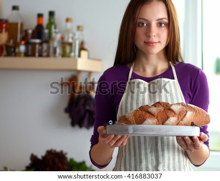 Young woman holding tasty fresh bread in her kitchen - stock photo