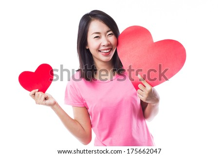 Young woman holding two of big and small red heart over head on white background - stock photo