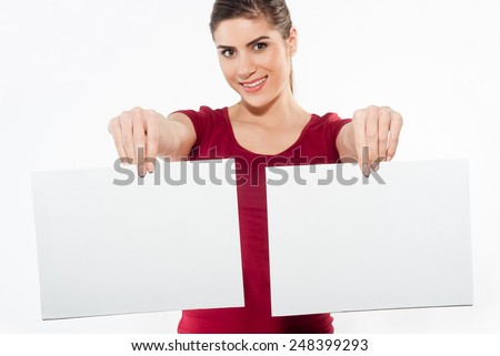 Young woman holding two white papers with copy space and smiling on a white background. Focus on hand  - stock photo
