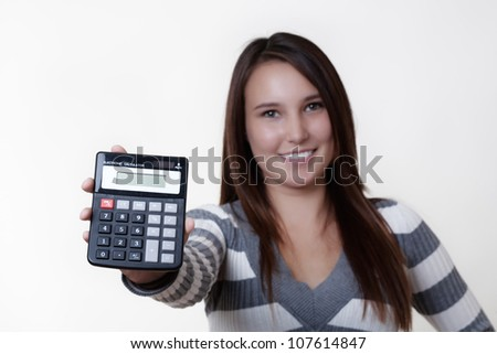 young woman holding up a calculator showing you what adds up - stock photo