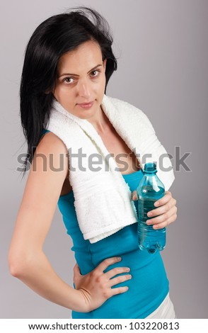Young woman holding water bottle.Brown background - stock photo