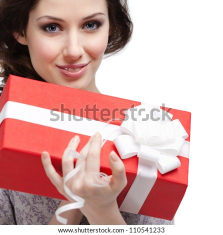Young woman holds a gift wrapped in red paper, isolated on white - stock photo