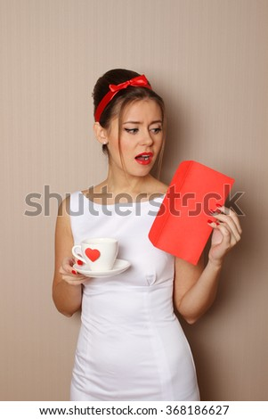 Young woman holds a mail and a cup with a red heart - stock photo