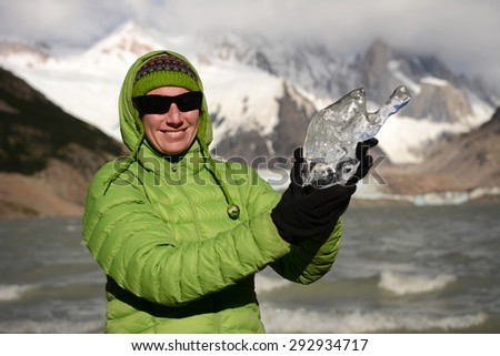 Young woman holds a piece of ice from glacier, Patagonia, Chile, South America - stock photo