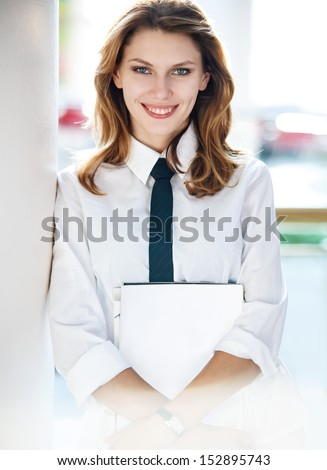 Young woman holds folders / women in a white button down shirt with black tie  - stock photo