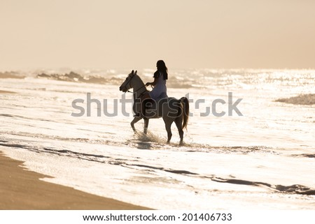 young woman horse ride in the water on beach - stock photo