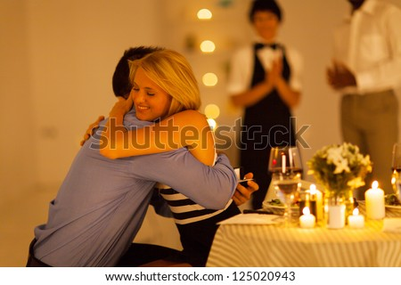 young woman hugging her boyfriend after he proposed in a restaurant - stock photo