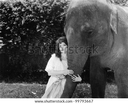 Young woman hugging the trunk of an elephant - stock photo