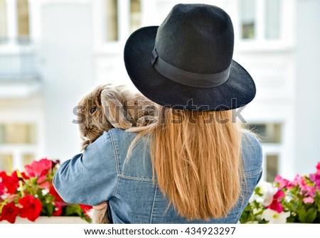 Young woman hugs big cute rabbit friend pet in her hands  - stock photo
