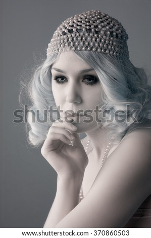 young woman in a beaded flapper hat with blond hair.   - stock photo