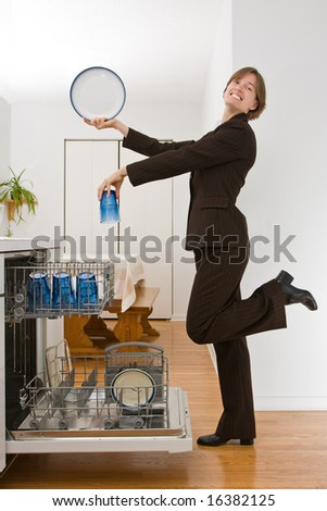 Young woman in a business suit loading the dishwasher in an exaggerated pose. - stock photo