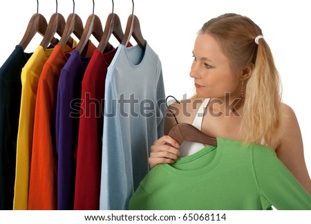 Young woman in a clothing store, choosing clothes to buy. - stock photo