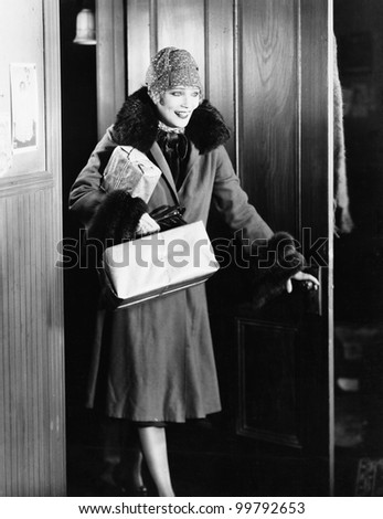 Young woman in a coat and hat entering into a room - stock photo