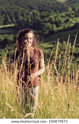 Young woman in a field - cross processed colors - stock photo