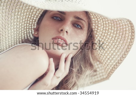 Young woman in a hat portrait. Bright soft colors. - stock photo