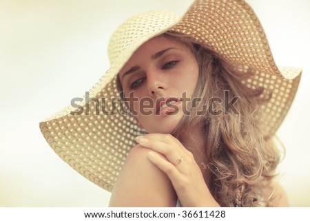 Young woman in a hat portrait. Yellow tint. - stock photo