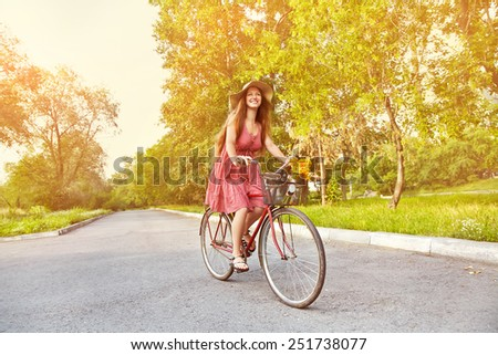 young woman in a hat riding a bicycle in a park. Active people. Outdoors - stock photo