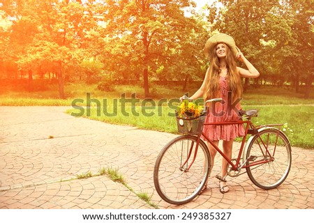 young woman in a hat with a bike in the park . Active people. Outdoors - stock photo