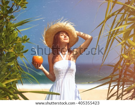 Young woman in a hat with coconut cocktail near the sea - stock photo