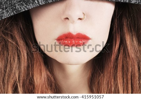 Young woman in a hooded jumper with red lipstick - stock photo