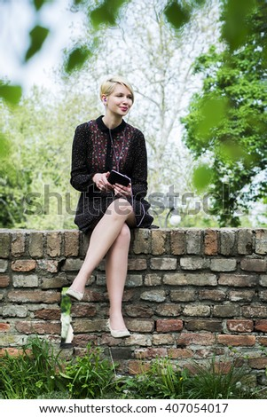 Young woman in a park on a wall enjoying  - stock photo