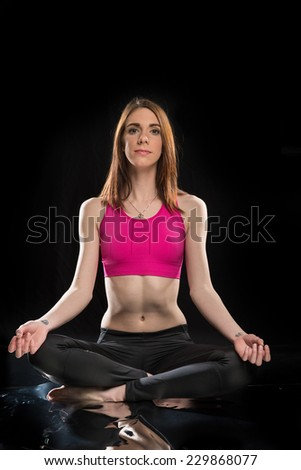 young woman in a pink sports bra and black tights on a black background in the lotus yoga pose.   - stock photo