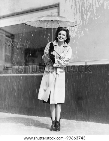 Young woman in a raincoat and umbrella standing in the rain - stock photo