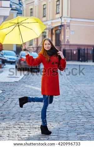 young woman in a red coat with yellow umbrella walks through the city - stock photo