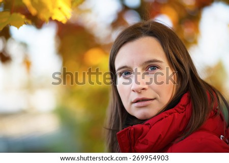 Young woman in a red jacket on a background of autumn leaves close-up. Bright colorful bokeh. Shallow depth of field. Selective focus on the near eye. Space for text. - stock photo