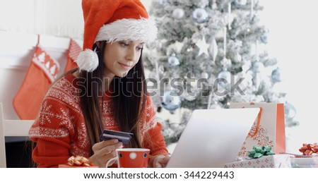 Young woman in a red Santa hat ordering Christmas gifts online sitting in front of the Xmas tree entering her bank card details on a laptop computer. - stock photo
