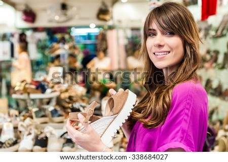 Young woman in a shoes shop, holding a shoe and smiling happy at the camera. - stock photo