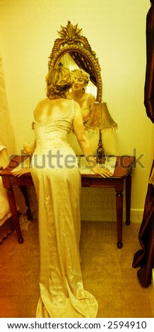 young woman in a silk pearl tight dress leaning on the table in front of the mirror - stock photo