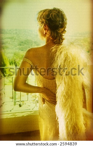 young woman in a silk pearl tight dress with feather boa on her shoulder standing outside - stock photo