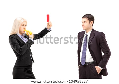 Young woman in a suit showing a red card and blowing a whistle to a young businessman, isolated on white background - stock photo