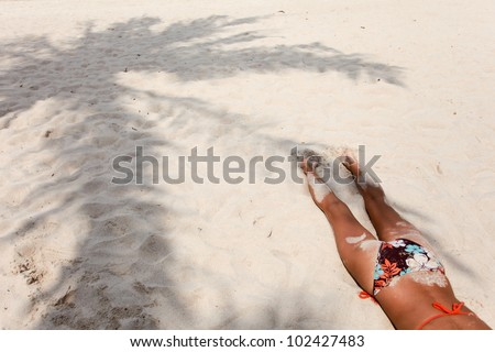 Young woman in a swimsuit lying on the sand at the beach. View from the back and shadow of palm trees - stock photo