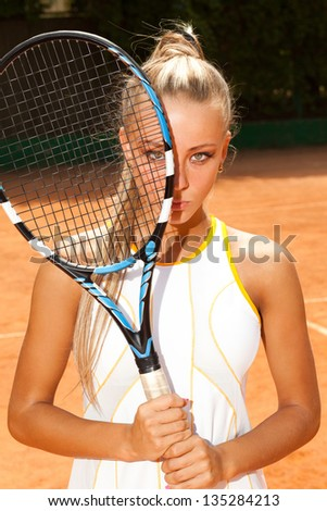 young woman in a tennis suit covered half her face with racket - stock photo