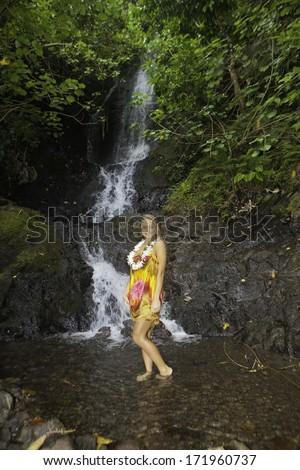 young woman in a tropical waterfall in Hawaii - stock photo