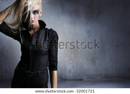 Young woman in a vampire look over grunge background - stock photo