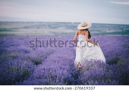 Young woman in a white dress and straw hat running in a lavender field with basket - stock photo