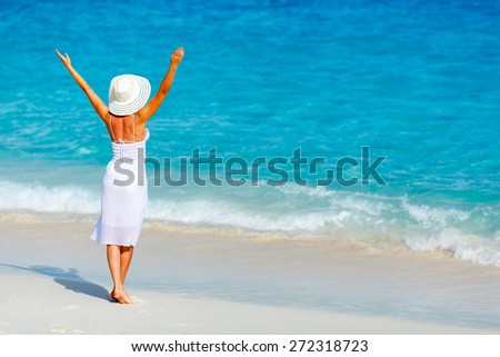 Young woman in a white dress walking on the tropical beautiful beach - stock photo