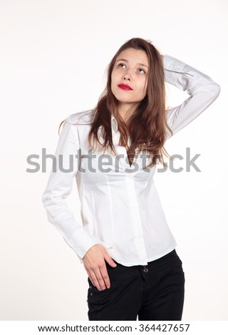 Young woman in a white shirt blouse on a light background. Young cheerful girl having fun. - stock photo
