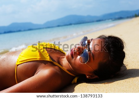 Young woman in a yellow swimsuit and sunglasses laying down on a sandy beach of Thailand on a sunny summer day - stock photo