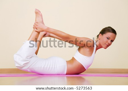 Young woman in a yoga position (Dhanurasana) - stock photo
