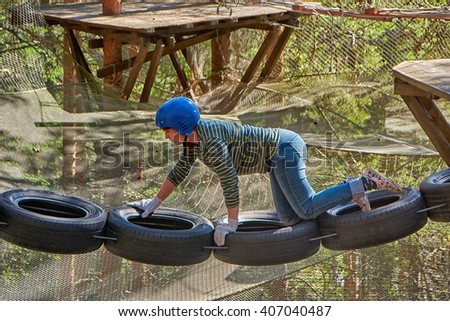 Young woman in adventure rope park - stock photo