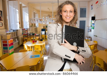 Young woman  in an elementary school classroom holding a laptop - stock photo