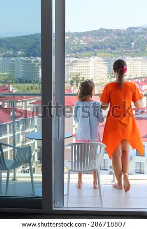 Young woman in an orange dress and daughter on the balcony in the room - stock photo
