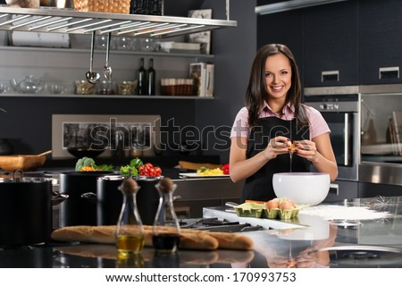 Young woman in apron breaking eggs for a dough on a modern kitchen - stock photo