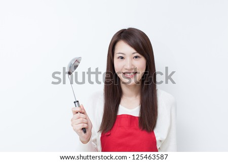 Young woman in apron holding ladle - stock photo