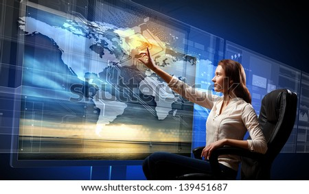 Young woman in armchair pushing icon on media screen - stock photo